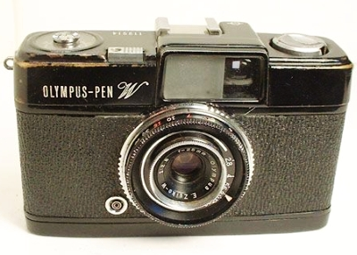 """""""Since this model sold for only two years, it is one of the more unusual models. It is basically the same as the Pen S, but had a slightly wider-angle, six-element, semi wide angle Zuiko 25mm (f2.8 - 22) manually-focusing lens. Focus was from 2 feet to infinity with click stops at 7 and 15 feet. Built-in tripod socket and cable release socket. On the front it says Pen W and it was only available in a black body. It also had a PC connection and a cold flash shoe. No meter. Shutter speeds of B, 1/8 - 1/250."""""""