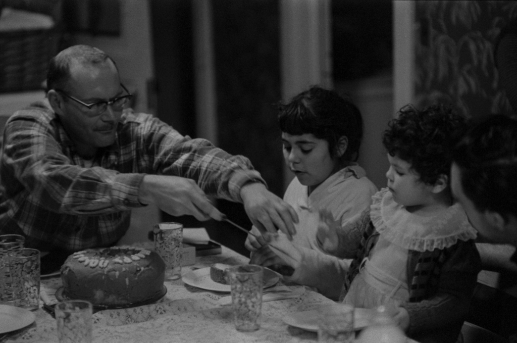 Gene sharing the cake with two of his children, 1956