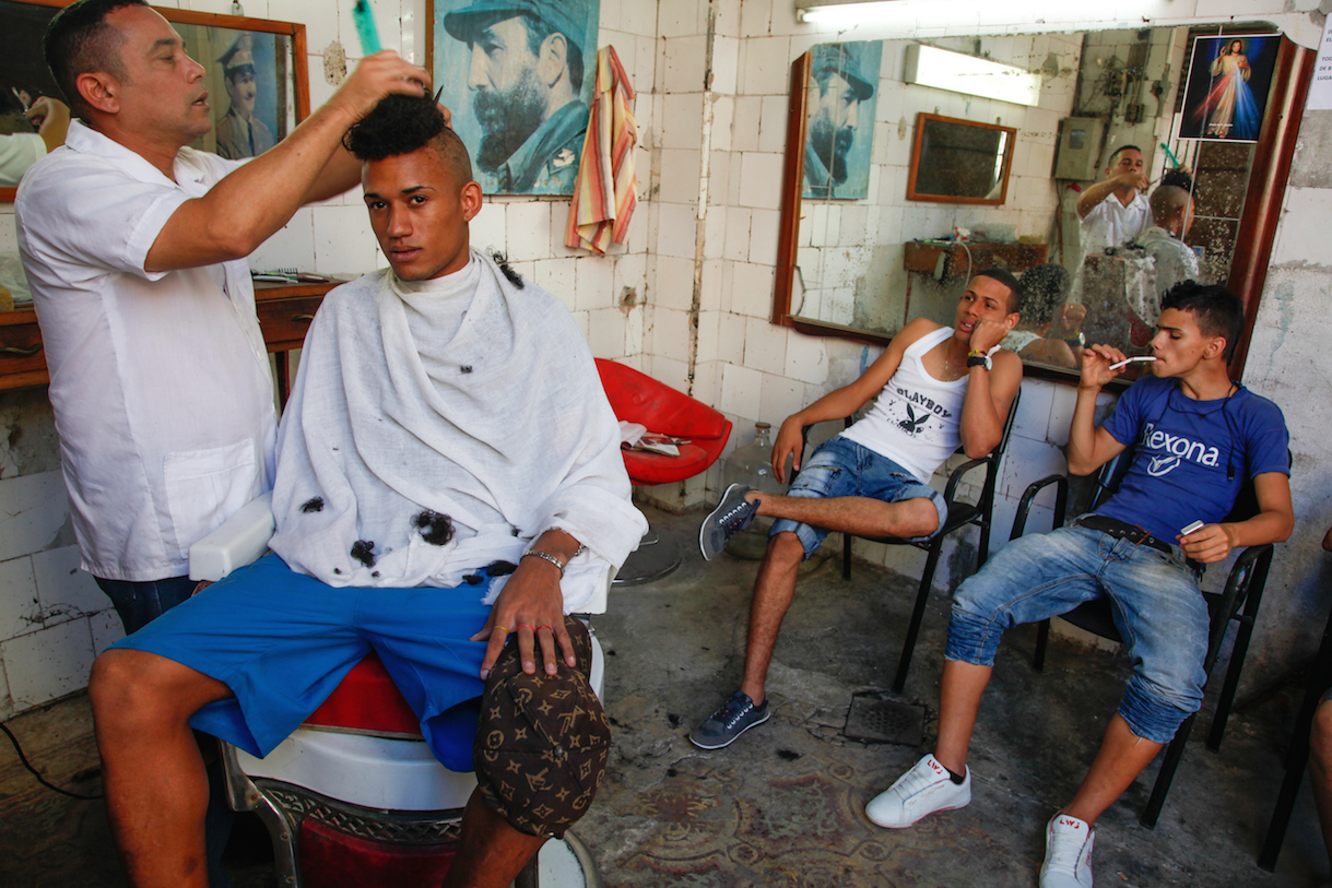 "Miguel at barber shop, 2012, © Mariette Pathy Allen. A lot of the women have boyfriends who are half their age. A lot of young gay men come from outside Havana and are ""kept"" by trans women,  who are mostly prostitutes because of the difficulty of finding work elsewhere due to their gender identification."
