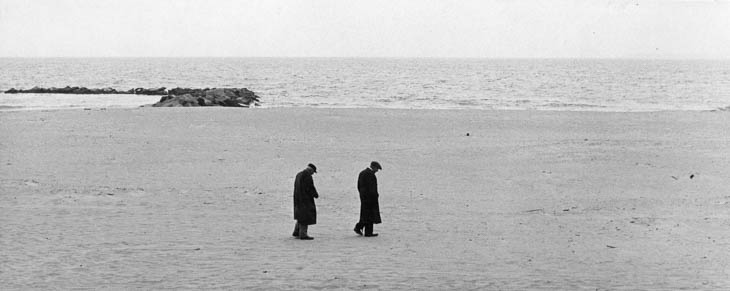 Two men walking on the beach, 1950