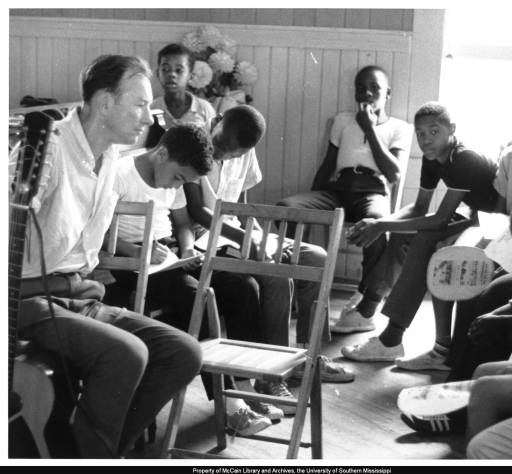 Pete Seeger meets with students in a Freedom School class at Mt. Zion Baptist Church in Hattiesburg, Mississippi, on August 4, 1964. Anthony Harris is on Seeger's left and Herbert Knox is to the right, leaning forward with his elbows on his knees. Photo by Hebert Randall. (c) USM Randall Archives.
