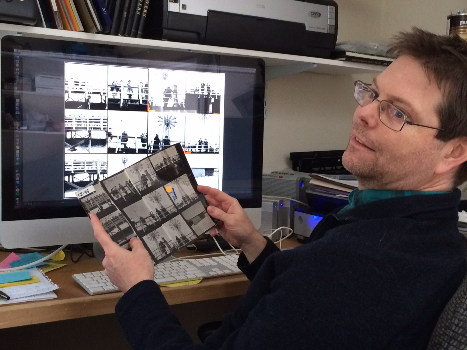 John holding up the original contact sheet ih comparison to screen view.
