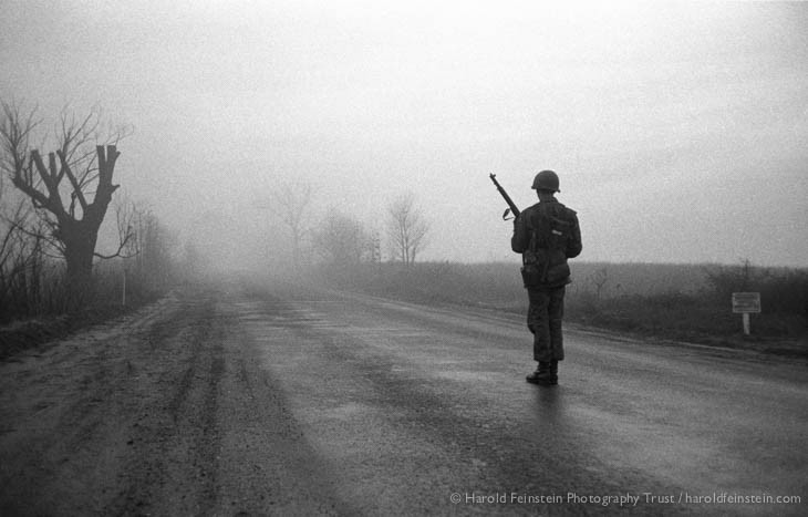 A lone soldier stands guard on an empty, foggy road, Fort Dix, New Jersey, 1952.