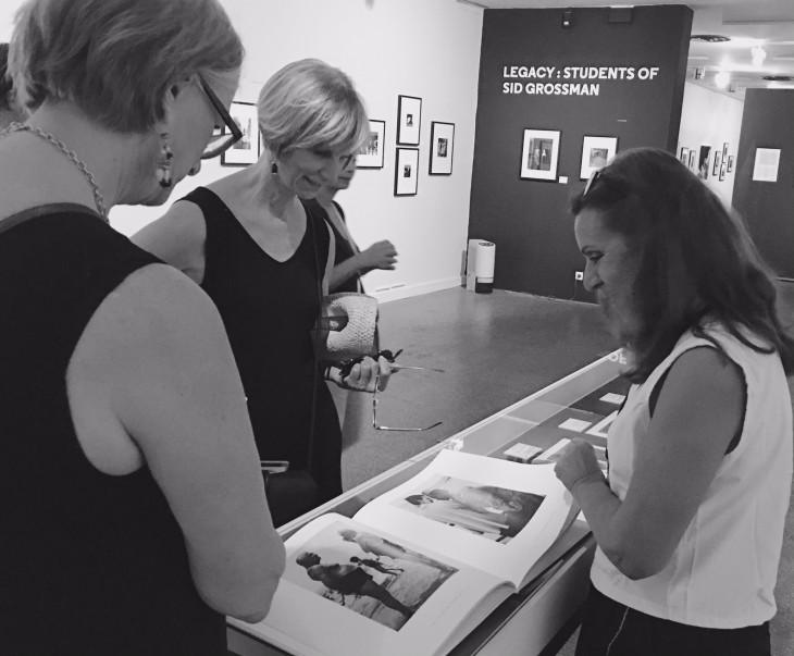 Beth Black and Ruth Thompson share Harold's Retrospective book with a docent at the Sid Grossman exhibition in Arles, France. © Judith Thompson