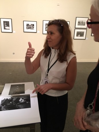 "A docent at the exhibition in Arles gives a thumbs up Feintein's photograph ""Draftees on the troopship home"", which she said was a favorite for many viewers."