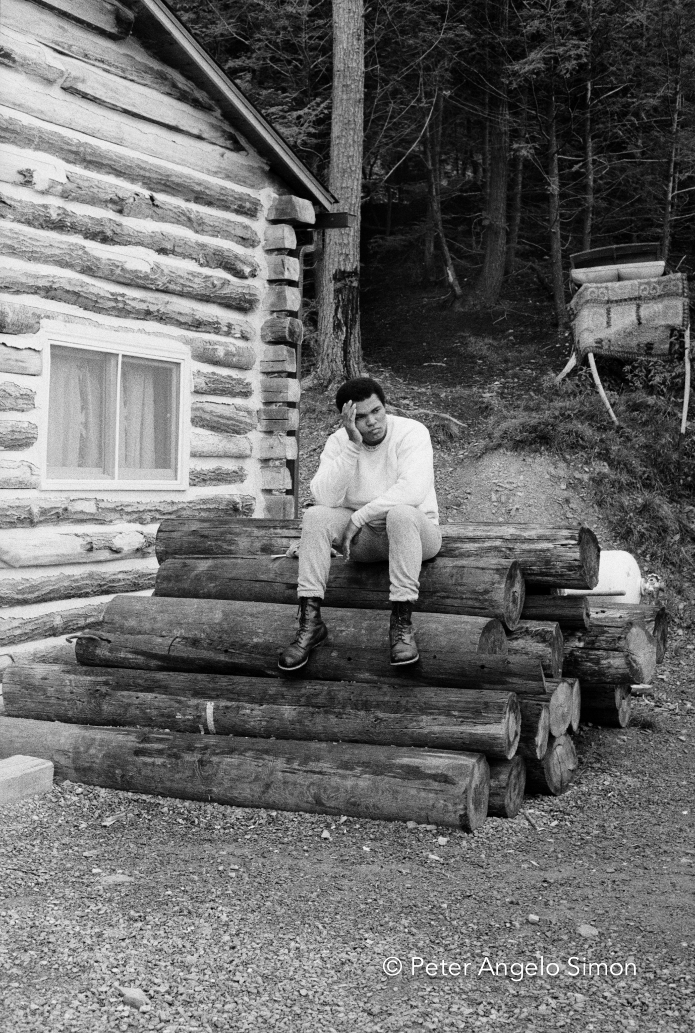 "Still without breakfast, Ali rests after the exertion of his dawn run. He called his Deer Lake, Pennsylvania camp ""Fighter's Heaven"" and said it was the best camp a fighter ever had.  He had specified that the camp's buildings be made of logs to give the place the old -time atmosphere he enjoyed. © Peter Angelo Simon, 1974"